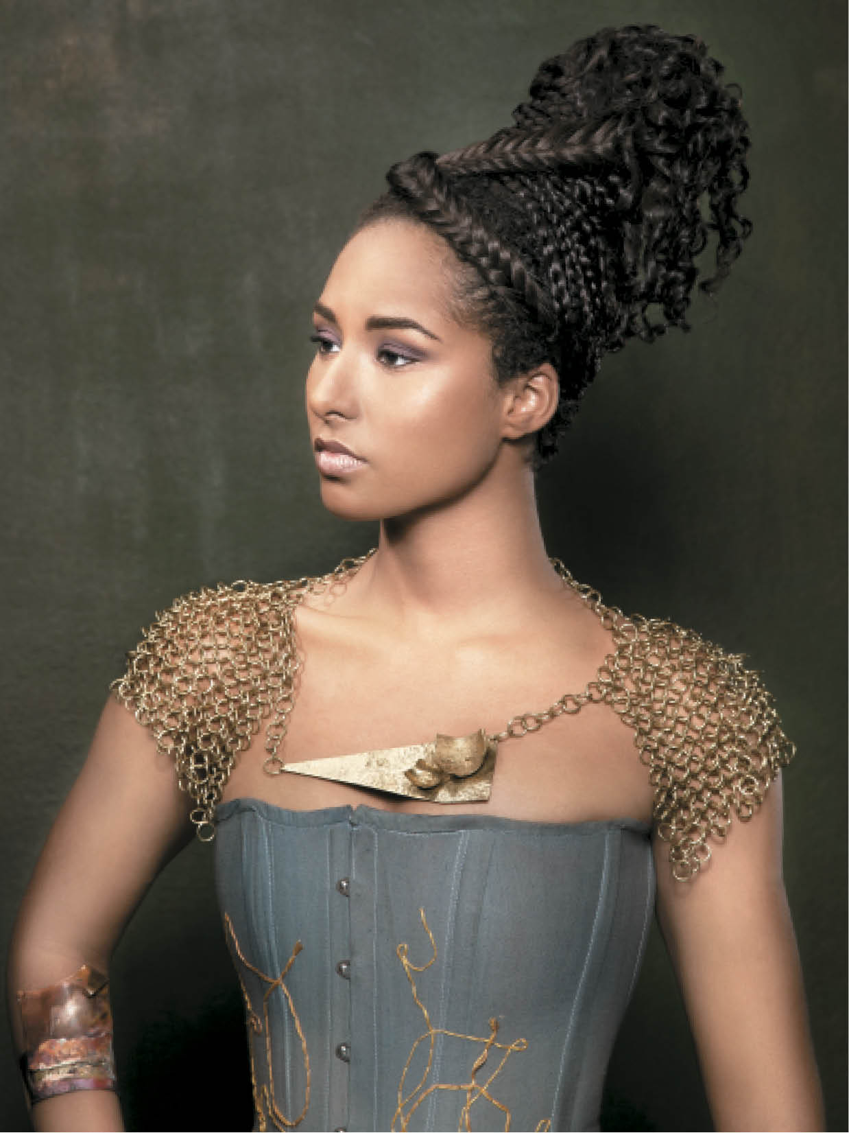 To achieve a braided updo, Sweet and Stokes finger-combed hair toward the crown and pinned it flat. Next, they sprayed the hair with water, covered it with fine tulle wrapped tightly to the head, and dried it. They pinned a donut mesh form at the crown as a base for tracks of textured hair extensions that were sewn into a cone shape. To finish, they added several braided extensions.