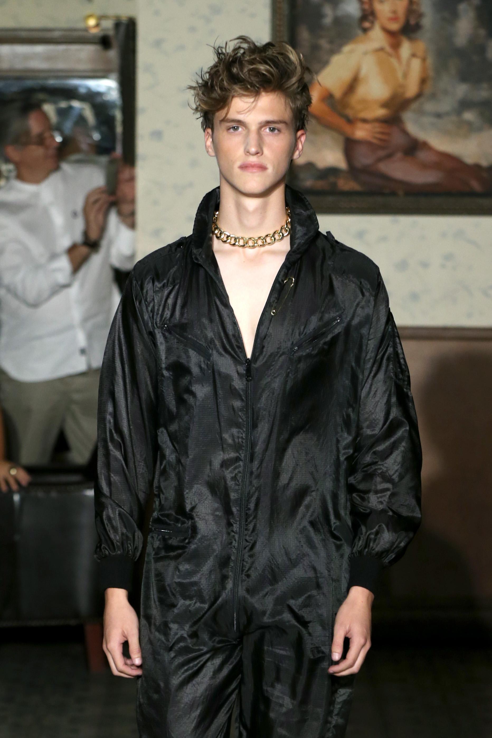 A male model walks the runway.