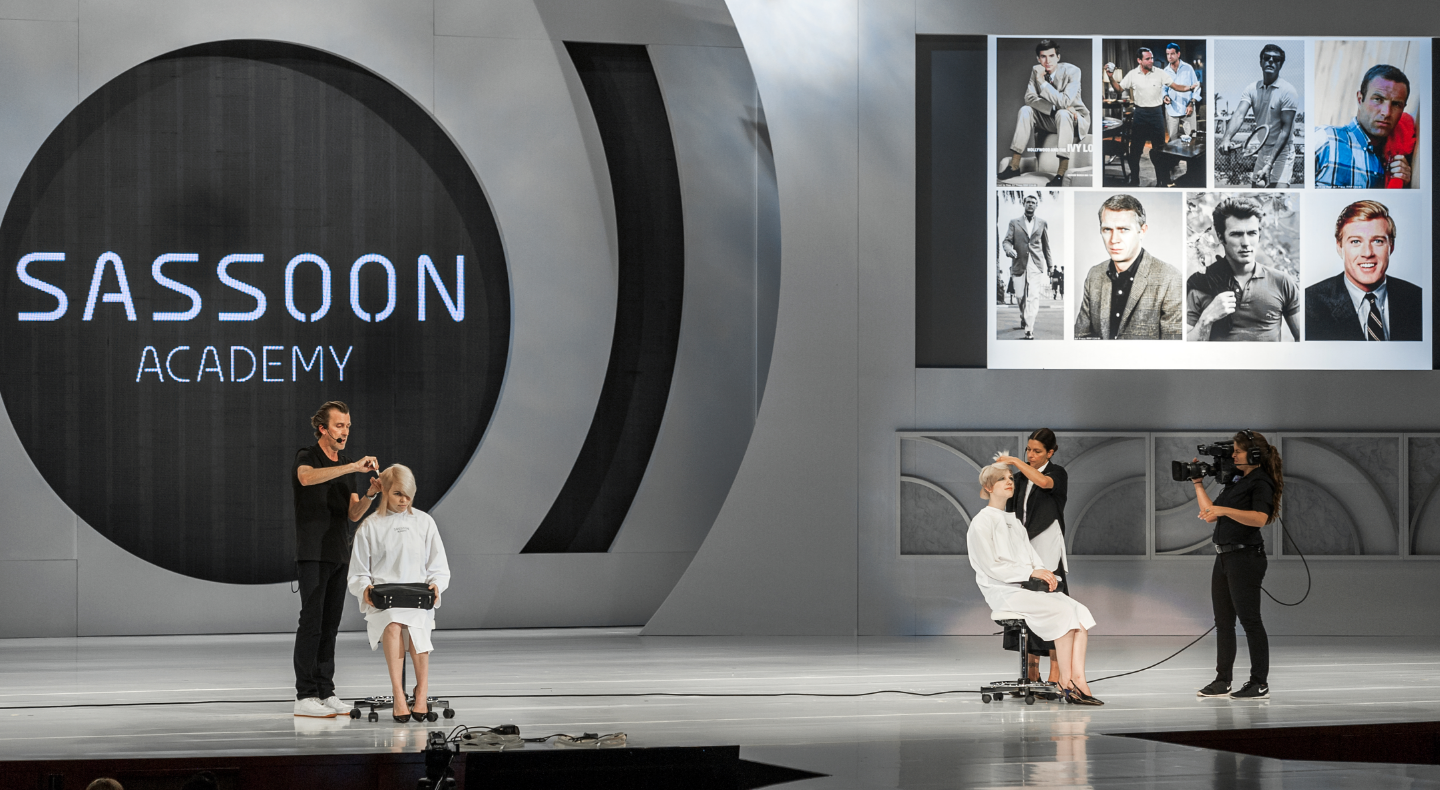 Mark Hayes & Traci Sakosits presenting on stage with Sassoon Academy