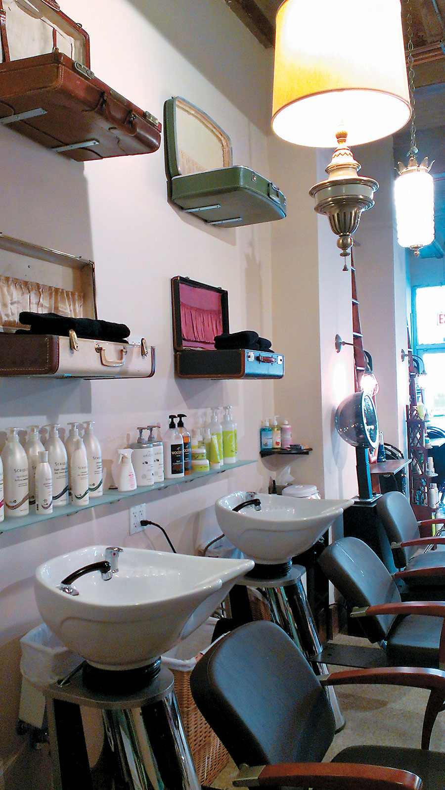 Vintage suitcases affixed to the wall above each shampoo bowl hold towels.