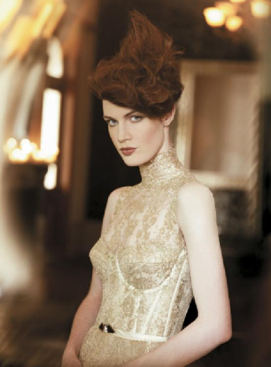Side-swept fringe and textured, wavy hair that rises to a point at the crown area are the focus of this unique updo created by Blain.