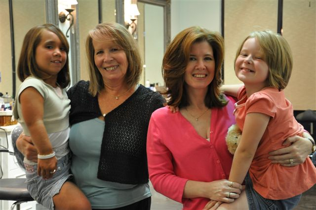 Sandy Vaughn (second from left) poses with her daughter Elaine Hirsch (second from right) and granddaughters Summer Opperud and Lauren Hirsch after each donating at least 10 inches of hair at the event.