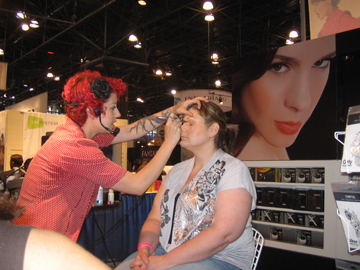 A makeup artist applying airbrush makeup to a show attendee at the Temptu booth