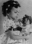 A girl with her look-alike Shirley Temple doll.