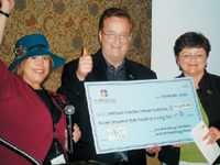 PureOlogy's Cheryl and Jim Markham present a check to Jane Langridge, CEO of NOCC.