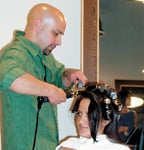Andres Medina, a color specialist at dk hair, discusses hair management techniques with a guest.