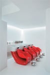 Curvy red shampoo chairs punctuate the predominantly white space at Cristiano Cora Studio.