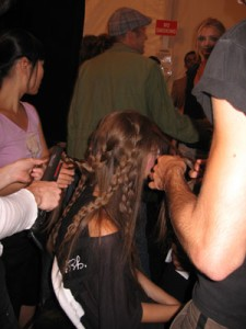 A model gets her hair braided to create beachy waves.