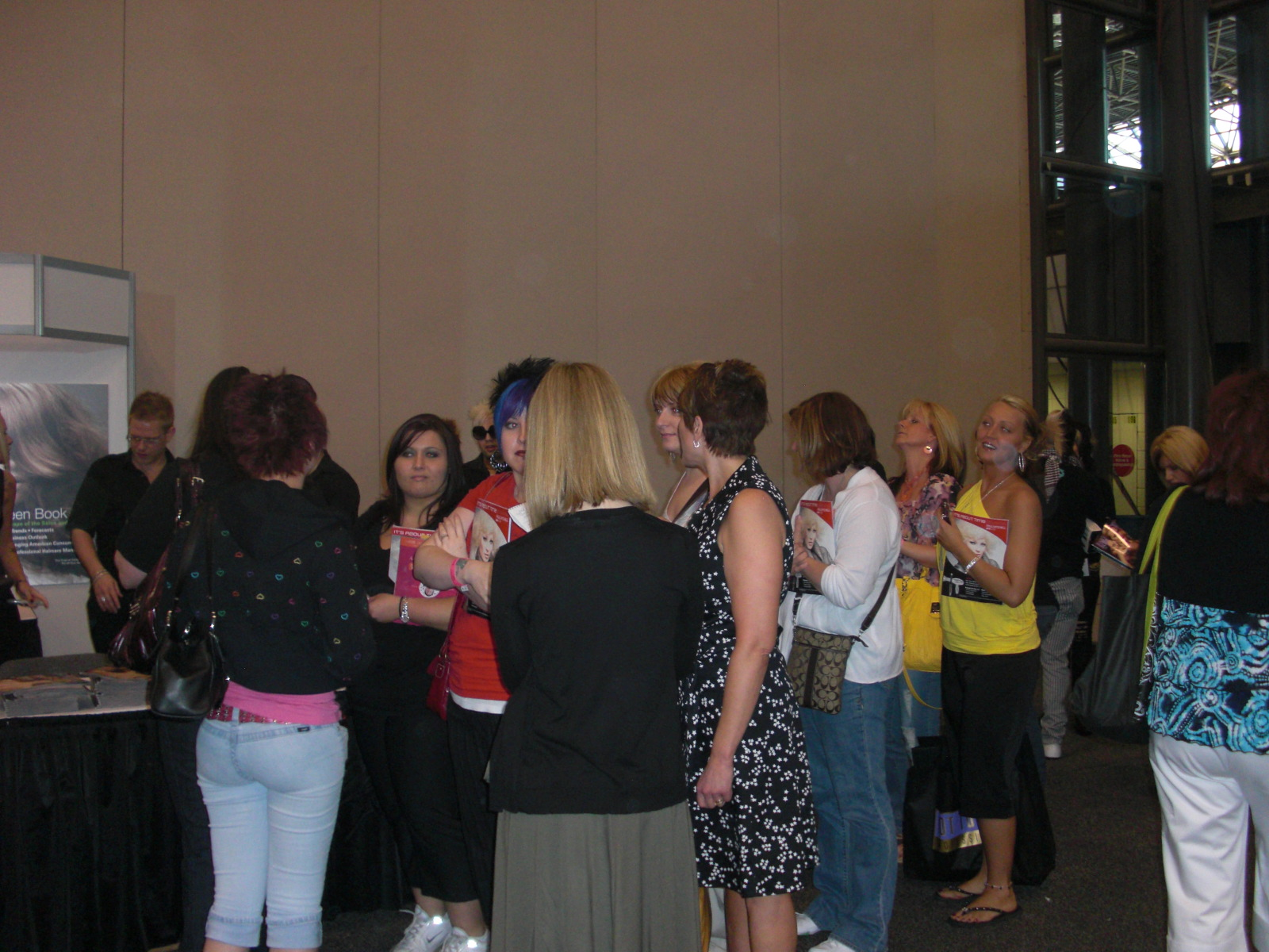 IBS attendees line up at the American Salon booth for autographs from the Shear Genius finalists