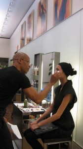 Rudy Miles applies makeup on a model.