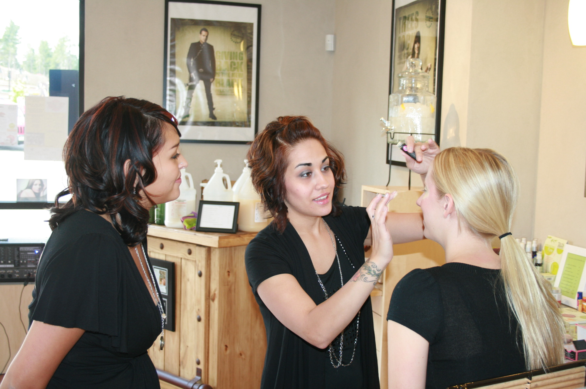 Splish's Veronica Potter applying makeup to Kristin McSherry, with Alyssa Romero looking on
