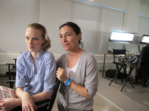 Key makeup artist for M.A.C Fulvia Farolfi with a model backstage at Juan Carlos Obando