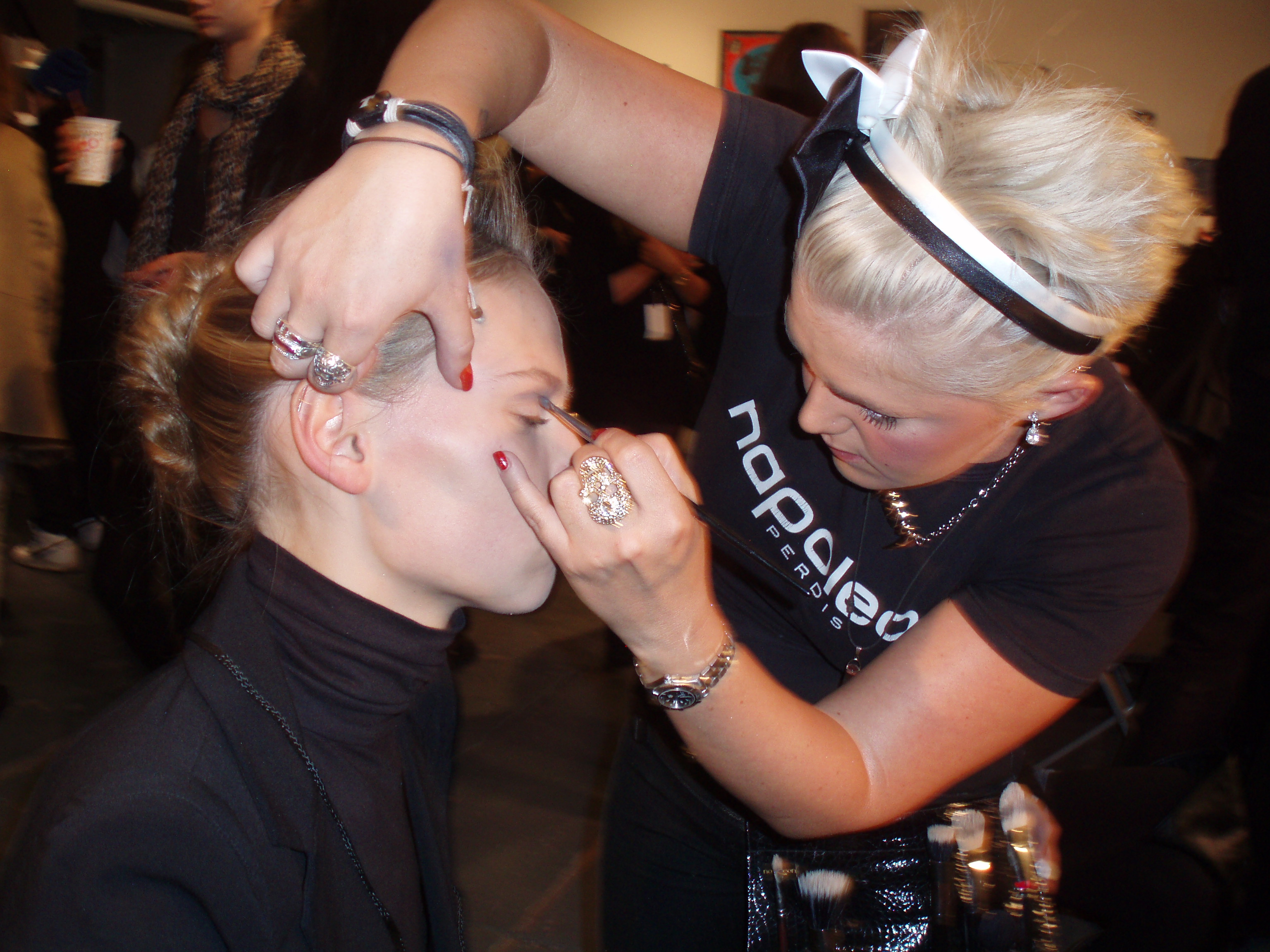 A makeup artist for Napoleon Perdis works on a model's eyes.