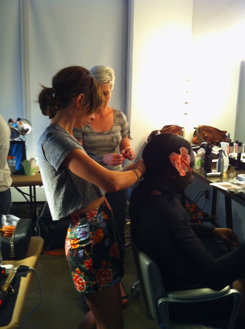 Lead stylist Ramona Eschbach styles a perfomance artist who was providing entertainment at the show