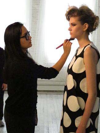 Makeup artist Chico Mitsui fine-tunes Kelsey's makeup on set.