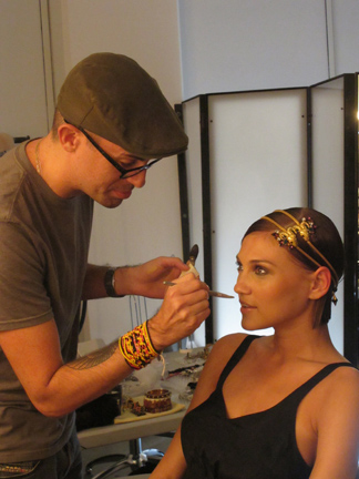 Makeup artist Robert Greene touches up the makeup.