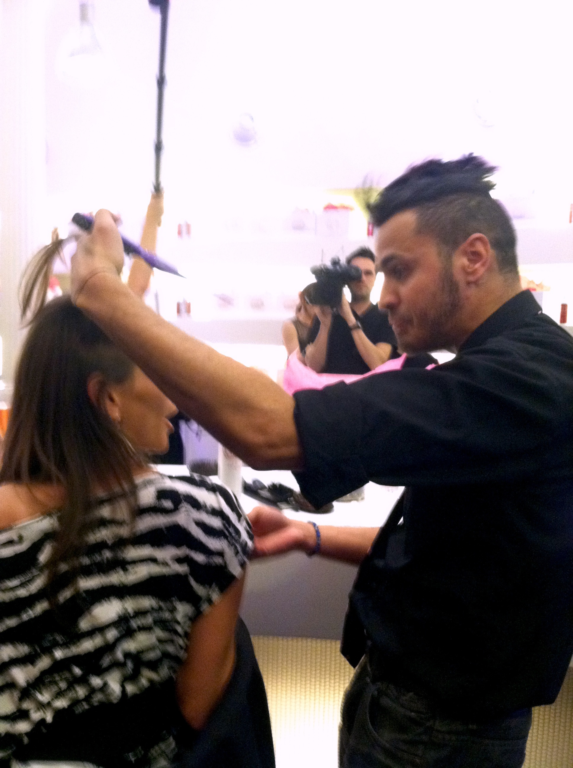 Stylist teaching a guest how to make the most of Over-the-Top Root Lift Spray