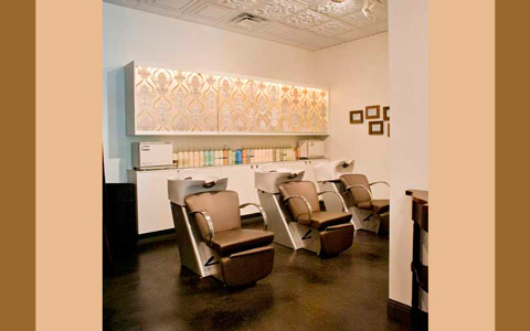 "Wanting total elegance and beauty, light color backwash stations were chosen from Takara Belmont instead of traditional black. Additional choices for a sophisticated style include silk fabric sandwiched between glass panels for the cabinets above the stations and framing the cosmetology licenses in gold, gilded frames. ""Making different choices in design and adding these special touches shows a bit more exclusivity than a regular salon,"" said Misko.  Photography Mark Seppala"