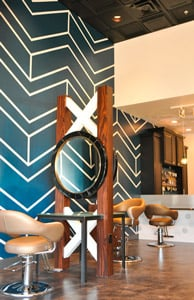 Prior to being a salon, the space was a restaurant; Phanomen completely reworked the rooms, but also used existing elements to enhance the design. For example the ceilings in the room are 15 feet high; Phanomen highlighted the height by adding the black paneled ceiling created by Ceilume to add dimension to the room. The blue wall with white zigzag stripes was custom-painted by Lisa Lozinak to be the workroom's focal point, rather than remaining to be the room's only large wall that reached the 15-foot ceiling.  Photography Lydia Lee