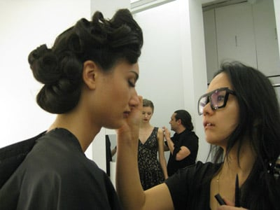 Makeup artist Chico Mitsui touches up model Catiane's makeup in between takes.
