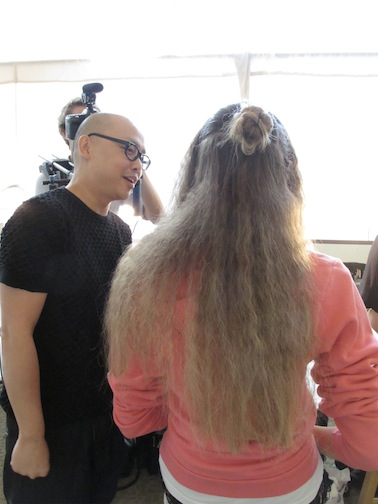 Makeup artist Daniel Martin for Lancome and a model with finished hair by TIGI's Nick Irwin backstage at Chris Benz