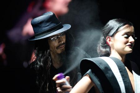 Takashi Kitamura sets a model's style with hairspray.