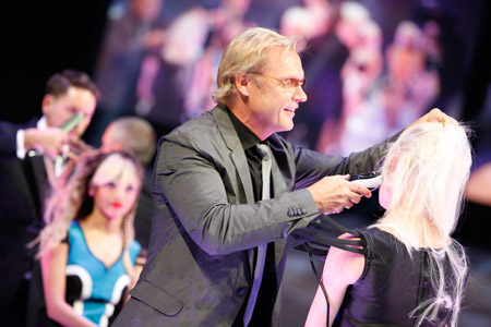 Scott Cole demonstrates a hair style on stage.