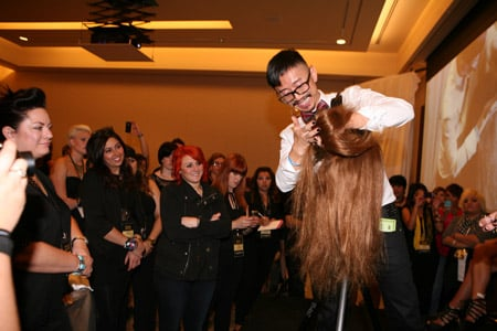 Noogie Thai educates attendees using a hair mannequin.