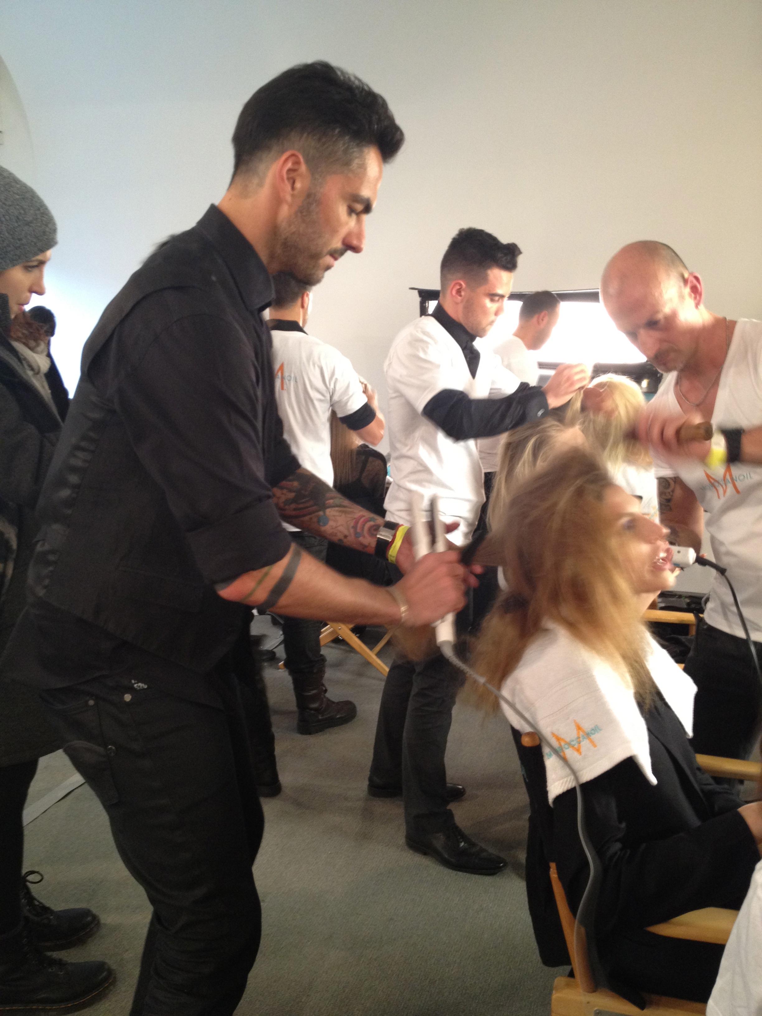 Antonio Corral Calero smoothes hair with flat-iron.