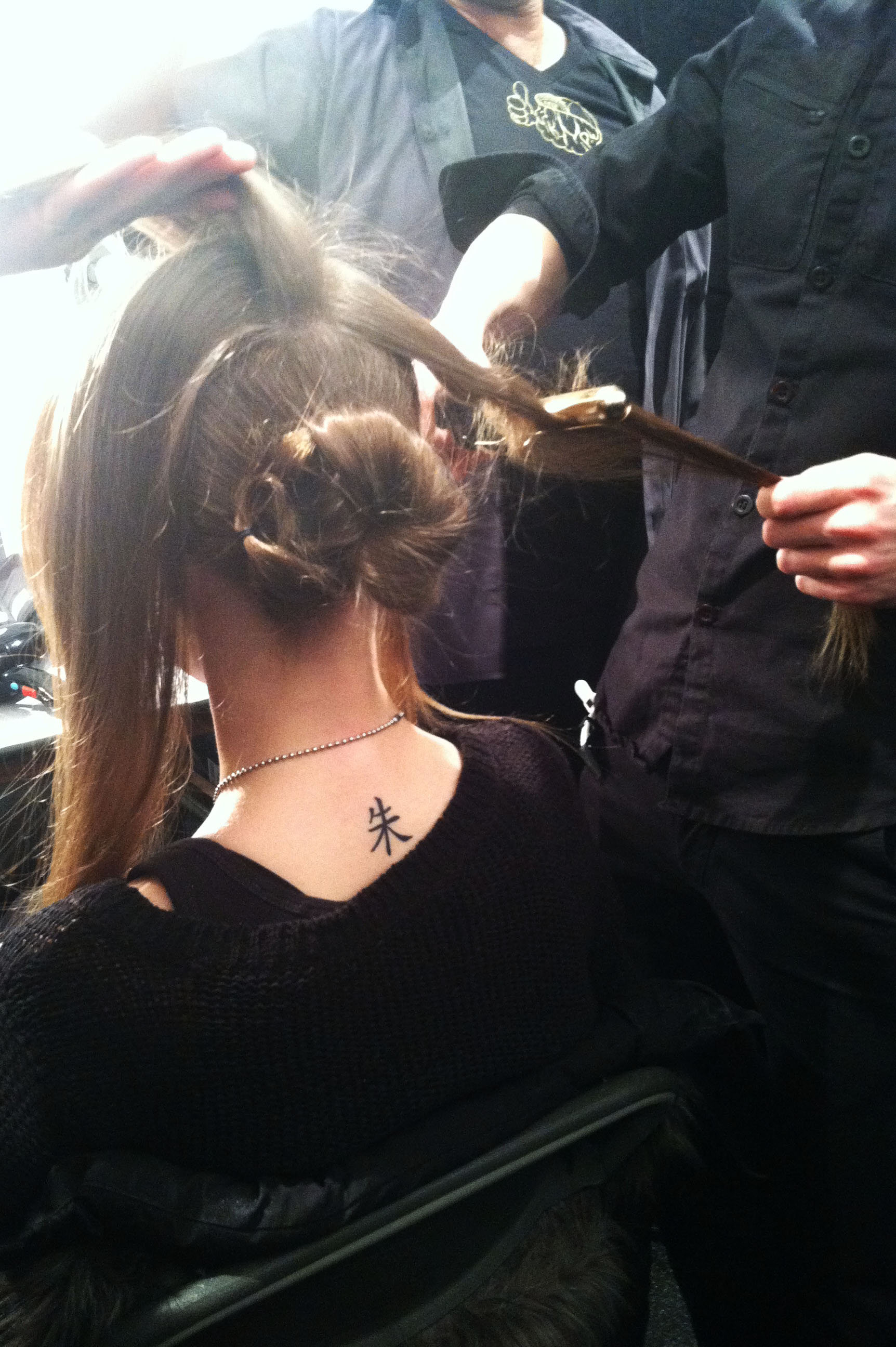 The top section of the hair is straightened, while one piece is held aside to be crimped