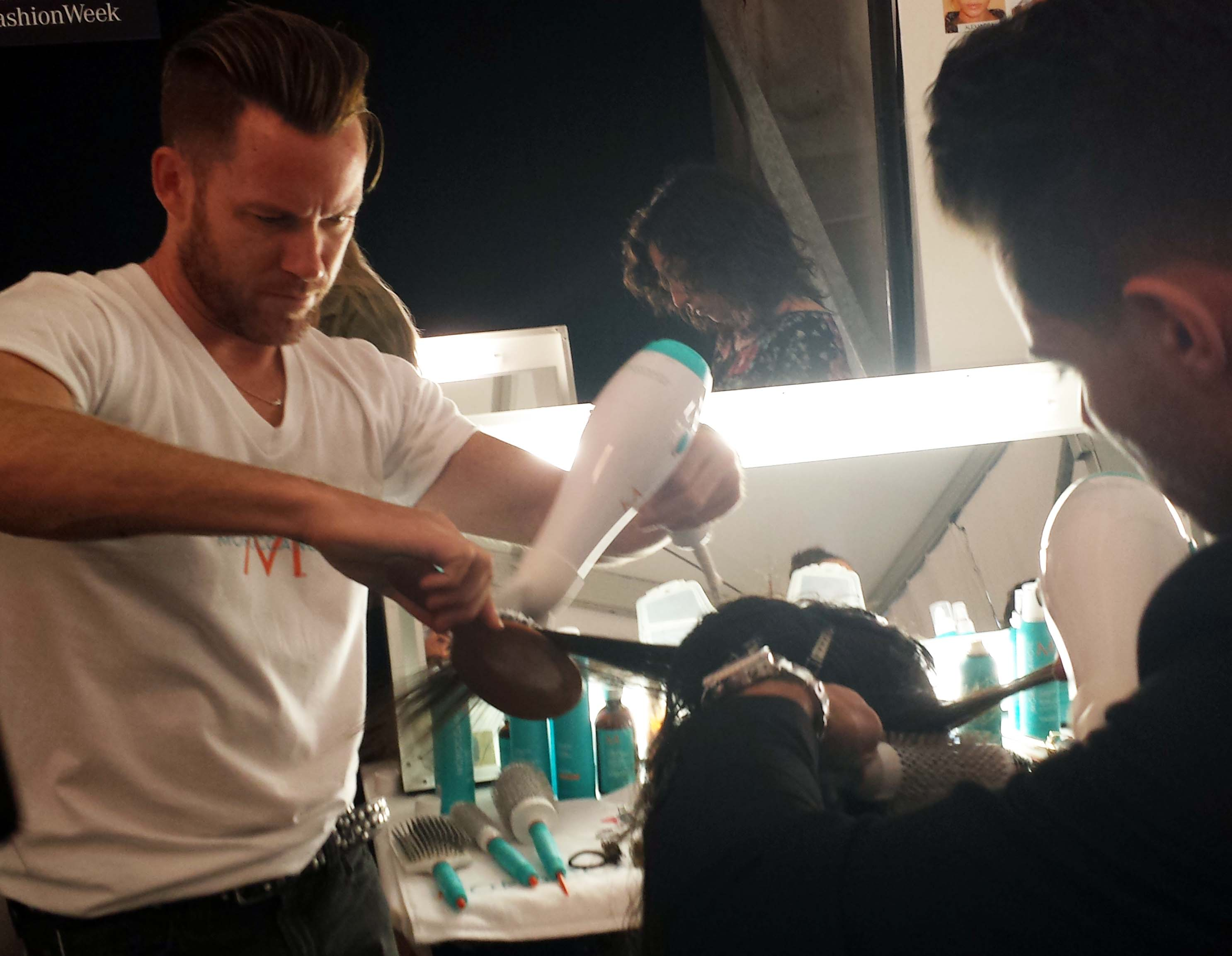 Two Moroccanoil stylist diligently blow dry the hair.