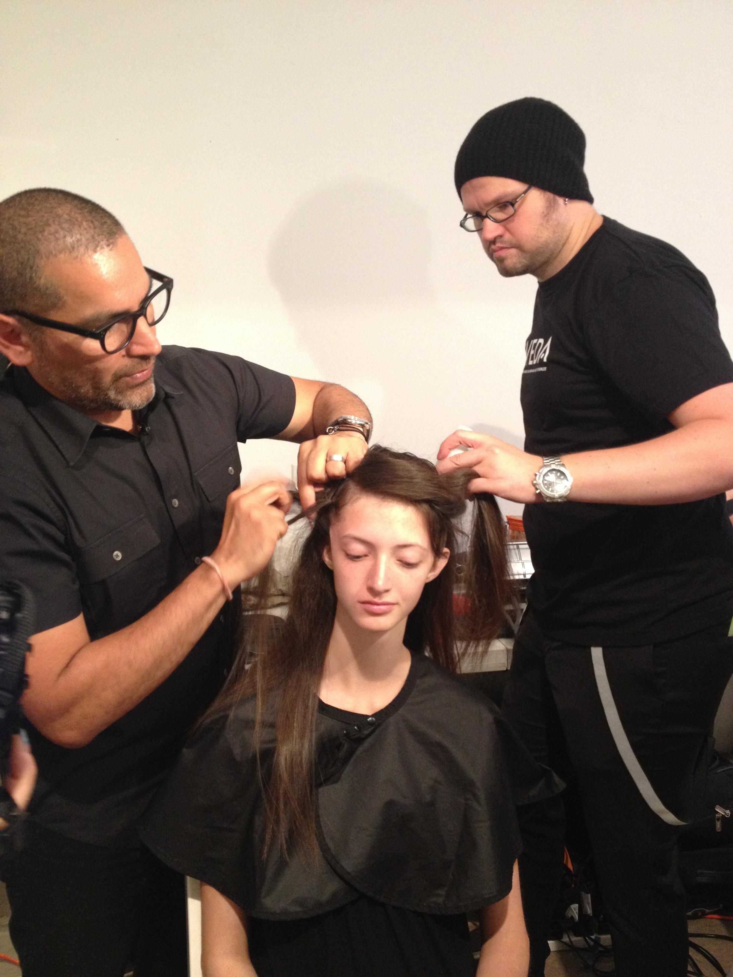 Allen Ruiz creates braids on either side of the head.