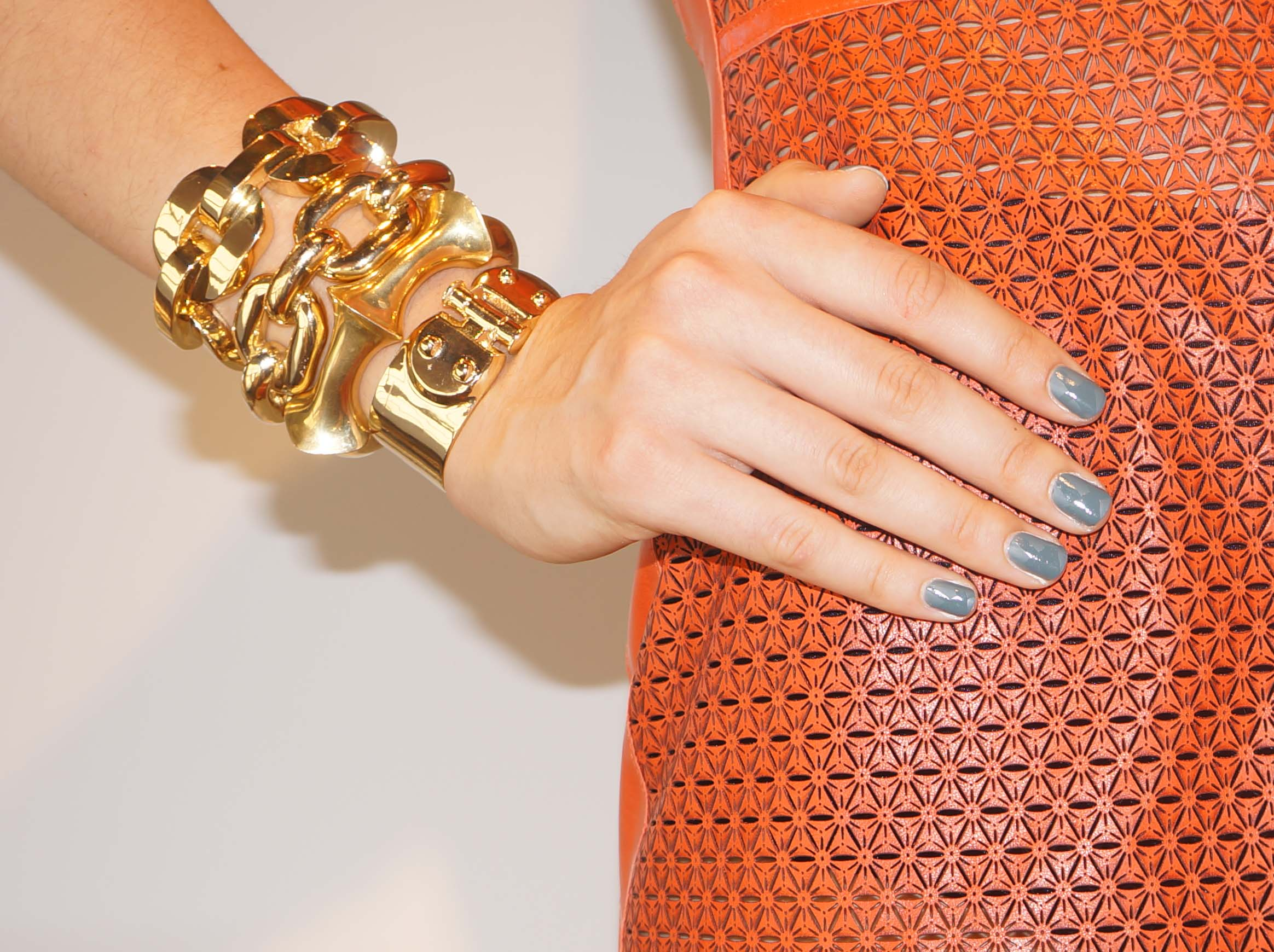 The nails compliment the neon orange dress