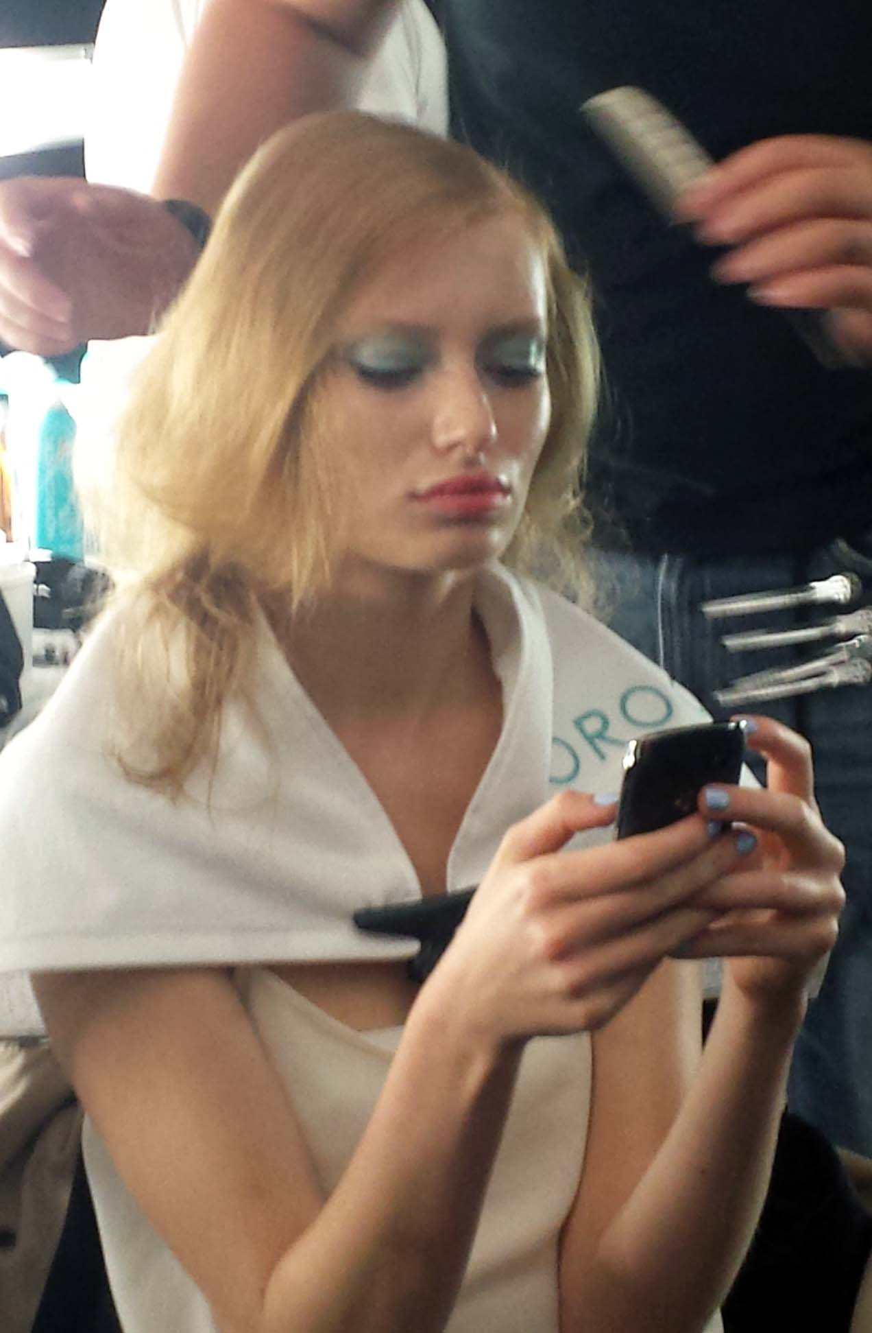 A model backstage getting her hair done.