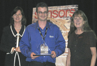 Eamonn Dillon holds the Best of Sensors Expo Gold award that his team at Analog Devices won. With him are Kate Dobson, VP of Questex Media Group's technology division (left), and Stephanie Henkel, Executive Editor of Sensors.