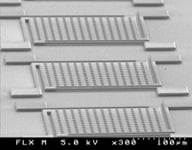 Figure 2. This SEM micrograph shows released poly-SiC microstructures fabricated from a 4 μm–thick film that was photolithographically patterned and etched. The extreme flatness of the suspension beams indicates a very low stress gradient.