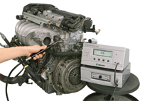 "Figure 1. With Sensistor's hydrogen-nitrogen-based leak detector, rugged enough for use on the plant floor, no vacuum is required and nothing gets wet. Here, the gas mixture has been pumped into an automobile engine, and the ""sniffer"" checks for sources of leakage."