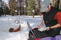 Figure 3. Researchers from the University of California, Merced, check the deployed Sensor Web. The pod is located just to the left of the upright mount, the sonic pinger used to determine snow depth is at the end of the cantilever to the right