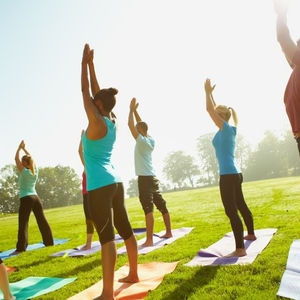 Young group of sportspeople taking a yoga class outdoors