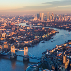 Aerial view of Tower Bridge and Canary Wharf skyline at sunset