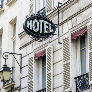 The period sign of a modest hotel, made of wrought iron and glass, on the facade of an old building with a vintage street light in a touristic district of Paris
