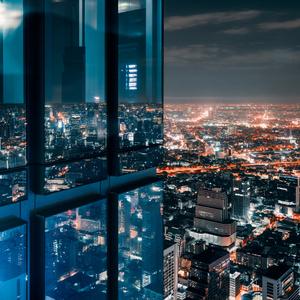 Corner glass window with glowing crowded city
