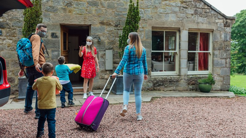 A shot of a young man and woman and their two young boys being greeted at a bed and breakfast by their host.