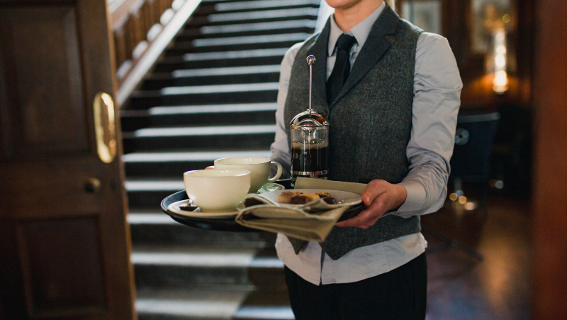 bartender holding a tray with coffee on