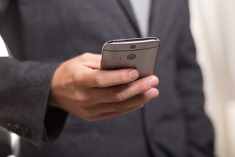 man in suit on smartphone