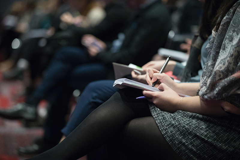People taking notes at a conference