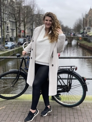 Sarah Engstrand stands by a bicycle overlooking a canal in Amsterdam