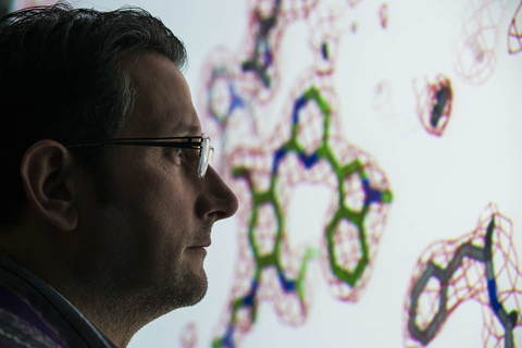 Male scientist looks at large screen
