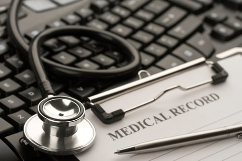computer keyboard with stethoscope and paper record