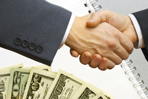 Two businessmen shaking hands over a pile of money